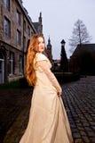 Muchacha en vestido victoriano en un viejo cuadrado de ciudad por la tarde imagenes de archivo