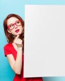 Muchacha en vestido y vidrios rojos con el tablero blanco Fotografía de archivo