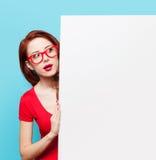 Muchacha en vestido y vidrios rojos con el tablero blanco Foto de archivo