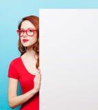 Muchacha en vestido y vidrios rojos con el tablero blanco Imagen de archivo
