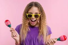 Muchacha en vidrios amarillos brillantes que ella baila con maracas en un fondo rosado Fotografía de archivo