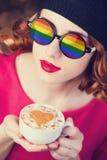 Muchacha en vidrios con la taza de café Imagenes de archivo