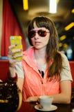 Muchacha en vidrios con un teléfono en un café Foto de archivo