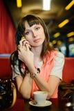 Muchacha en vidrios con un teléfono en un café Imágenes de archivo libres de regalías