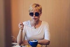 Muchacha en vidrios con una cuchara del café Fotografía de archivo libre de regalías