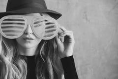 Muchacha en vidrios divertidos chica joven linda de la moda con los vidrios divertidos y el sombrero verde Imagenes de archivo