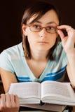 Muchacha en vidrios en la lectura de un libro Foto de archivo