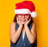 Muchacha en vidrios rojos y Santas Imagen de archivo libre de regalías