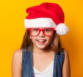 Muchacha en vidrios rojos y Santas Imágenes de archivo libres de regalías