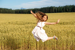Muchacha en vuelo de un salto en un campo de trigo en verano Imágenes de archivo libres de regalías