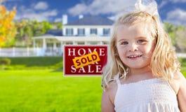 Muchacha en yarda con la muestra y la casa vendidas de Real Estate imagen de archivo libre de regalías
