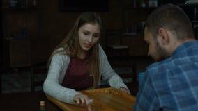 Muchacha encantadora alegre que juega a backgammon en casa almacen de video