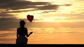 Muchacha encantadora con el globo rojo que disfruta de puesta del sol metrajes