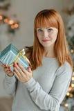 Muchacha encantadora con el pelo recto que sonríe y que sostiene un regalo en a Foto de archivo libre de regalías