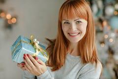 Muchacha encantadora con el pelo recto que sonríe y que sostiene un regalo en a Fotos de archivo libres de regalías