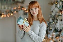 Muchacha encantadora con el pelo recto que sonríe y que sostiene un regalo en a Imagen de archivo libre de regalías