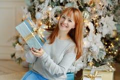 Muchacha encantadora con el pelo recto que sonríe y que sostiene un regalo en a Imágenes de archivo libres de regalías