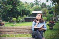 Muchacha encantadora del inconformista que piensa algo mientras que lee el libro rojo Fotos de archivo libres de regalías