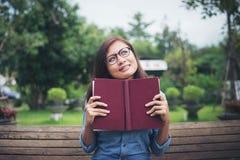 Muchacha encantadora del inconformista que piensa algo mientras que lee el libro rojo Imagen de archivo