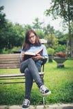 Muchacha encantadora del inconformista que se relaja en el parque mientras que libro leído, Enjo Fotografía de archivo