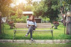 Muchacha encantadora del inconformista que se relaja en el parque mientras que libro leído, Enjo Imagen de archivo libre de regalías