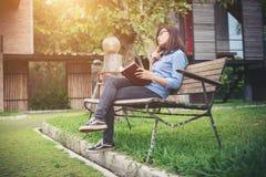 Muchacha encantadora del inconformista que se relaja en el parque mientras que libro leído, Enjo Fotografía de archivo libre de regalías