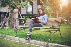 Muchacha encantadora del inconformista que se relaja en el parque mientras que libro leído, Enjo Foto de archivo libre de regalías