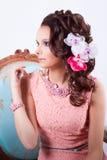 Muchacha encantadora en un vestido rosado y con las flores en su cabeza Foto de archivo