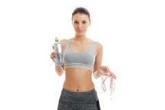 Muchacha encantadora flaca de la aptitud que sostiene una botella de agua y de una cinta métrica Imagenes de archivo
