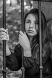 Muchacha encantadora joven del adolescente con el pelo oscuro largo que se sienta detrás de barras en una prisión en la fortaleza Fotos de archivo