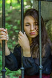 Muchacha encantadora joven del adolescente con el pelo oscuro largo que se sienta detrás de barras en una prisión en la fortaleza Foto de archivo libre de regalías