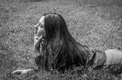 Muchacha encantadora joven el adolescente con el pelo largo que se acuesta y que descansa sobre la hierba verde mientras que cami Imagenes de archivo