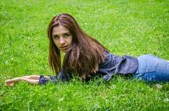 Muchacha encantadora joven el adolescente con el pelo largo que se acuesta y que descansa sobre la hierba verde mientras que cami Foto de archivo