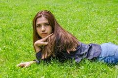 Muchacha encantadora joven el adolescente con el pelo largo que se acuesta y que descansa sobre la hierba verde mientras que cami Fotografía de archivo