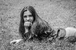 Muchacha encantadora joven el adolescente con el pelo largo que se acuesta y que descansa sobre la hierba verde mientras que cami Imágenes de archivo libres de regalías
