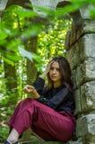 Muchacha encantadora joven el adolescente con el pelo largo que se sienta en las ruinas tristes de una ventana de piedra antigua  Imagenes de archivo