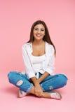 Muchacha encantadora joven que se sienta en piso en la actitud del loto, sonriendo Fotos de archivo