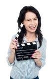 Muchacha encantadora joven que sostiene clapperboard Fotos de archivo libres de regalías
