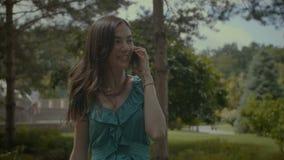Muchacha encantadora que charla en el teléfono móvil al aire libre almacen de video
