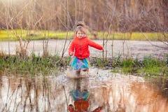 Muchacha encantadora que corre en charco grande Foto de archivo