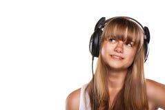 Muchacha encantadora que escucha una música en auriculares Foto de archivo