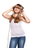 Muchacha encantadora que escucha una música en auriculares Imagen de archivo libre de regalías