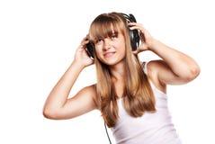 Muchacha encantadora que escucha una música en auriculares Fotos de archivo