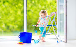Muchacha encantadora que lava una ventana en el sitio blanco Fotografía de archivo libre de regalías