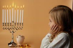 Muchacha encantadora que mira velas ardiendo del menorah foto de archivo