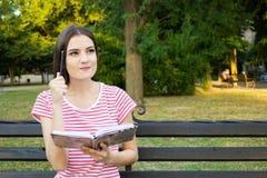 Muchacha encantadora que piensa algo mientras que lee un libro en el parque verde Foto de archivo