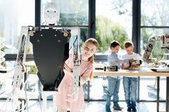 Muchacha encantadora que presenta detrás de una parte posterior humana del robot Imagen de archivo libre de regalías