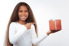 Muchacha encantadora que señala en la caja de regalo con el finger Fotografía de archivo