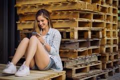 Muchacha encantadora que se sienta en una plataforma usando el teléfono elegante Fotografía de archivo libre de regalías