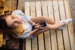 Muchacha encantadora que se sienta en una plataforma usando el teléfono elegante Imagenes de archivo